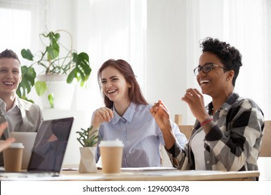 Happy joyful diverse business people laughing at funny joke talking at work break, cheerful corporate team office workers multi-ethnic young coworkers having fun engaged in teambuilding activity