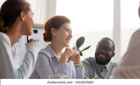 Happy joyful diverse business people talking laughing at funny joke focus on attractive female. Work break, interesting last news discussion, engaging in teambuilding activity, sharing ideas concept