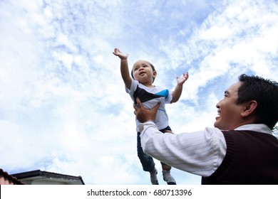 happy joyful father having fun throws up child in the air