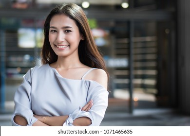happy joyful girl face; cheerful smiling woman portrait; positive relaxed happy asian woman smiles in outdoor city environment;