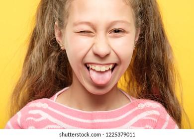 happy joyful girl sticking tongue out. mischievous childish behavior and naughtiness.