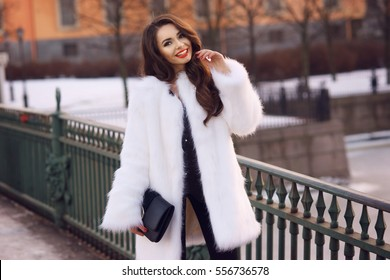 Happy joyful girl in white fur coat holding black leather handbag and walking down the street on a cold winter evening at sunset.