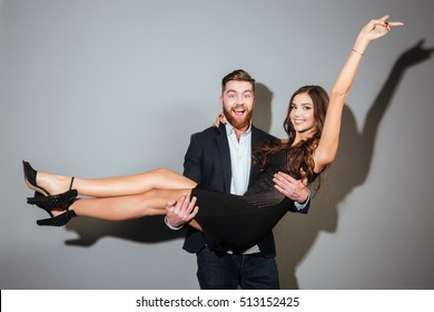 Happy joyful man in suit holding his girlfriend in his arms over gray background
