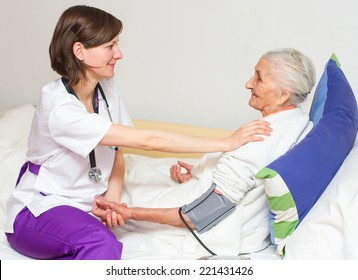 Happy joyful nurse caring for  an elderly woman  helping her days in nursing home.