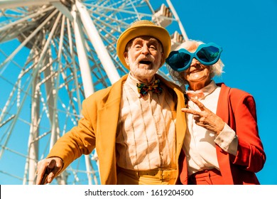 Happy joyful old couple in funny accessories near attraction stock photo