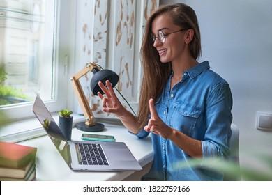 Fröhlich fröhliche Lächlerin, die in Gebärdensprache lernt und kommuniziert online auf einem Laptop bei gemütlichem Komfort zu Hause am Fenster
