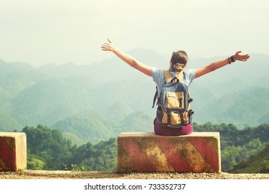 Happy and joyful traveller with raised hands sits at the edge of the road enjoying view at mountains.Mountains landscape, travel to Asia, happiness emotion, summer holiday concept