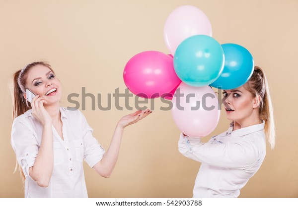 Happy joyful two girls having fun, playing with colorful balloons and talking on mobile phone. Holidays, celebration friendship and technology concept.