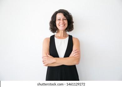 Fröhliche, fröhliche Frau in lockerer Haltung auf weißem Studiohintergrund. Porträt einer fröhlichen Geschäftsfrau mittleren Alters, deren Arme sich vor der Kamera lächeln. Frauenporträtkonzept
