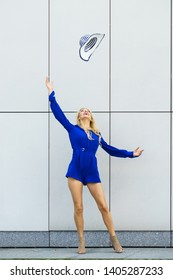Happy joyful woman wearing blue jumpsuit having fun throwing her sun hat. Fashion model and summer outfit.