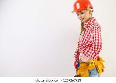 Happy joyful woman wearing helmet and checked shirt being positive about construction work.