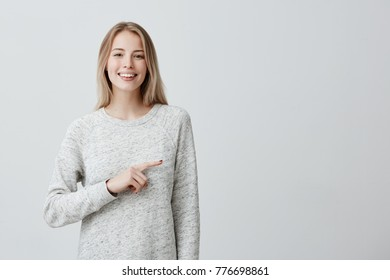 Happy joyful young blonde woman with dyed hair smiling broadly pointing with index finger at wall with copy space for promotional content. Emotional smiling beautiful girl advertising something.