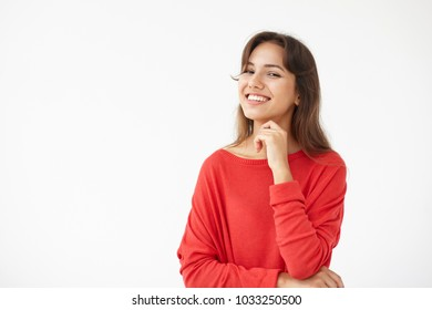 Happy joyful young Hispanic woman wearing red oversize top rejoicing at funny joke or birthday gift, looking at camera with cheerful charming smile. Brunette student girl having fun, posing in studio