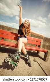 Happy joyful young woman wearing roller skates sitting on bench enjoying herself. Female being sporty having fun during summer time.