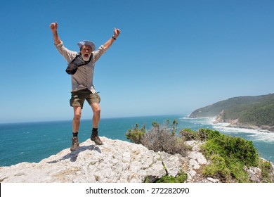 Happy jumping old man against beach background. Shot on the Otter trail in the Tsitsikamma National Park, Garden Route area, Western Cape, South Africa.