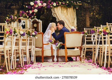 happy just married bride and groom sitting on chairs and kissing after vedding ceremony Montenegro