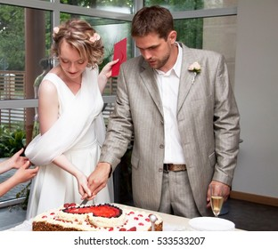 Happy just married couple cuting wedding cake