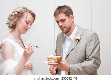 Happy just married couple eating wedding cake