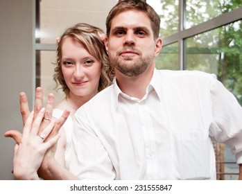 Happy just married man and woman show their wedding rings