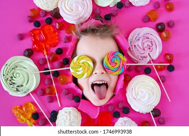 Happy kid with assorted sweets and lollipops on pink background. Child loves sweets, Funny family time. Little boy eats Lolly pop sweet