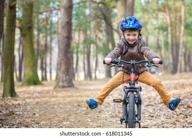 Happy kid boy of 3 or 5 years having fun in autumn forest with a bicycle on beautiful fall day. Active child wearing bike helmet. Safety, sports, leisure with kids concept