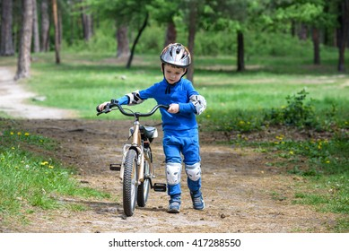 Happy kid boy of 4 years having fun in autumn forest with a bicycle on beautiful fall day. Active child making sports. Safety, sports, leisure with kids concept.