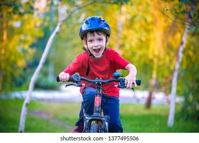Happy kid boy of 6 years having fun in autumn forest with a bicycle on beautiful fall day. Active child making sports. Safety, sports, leisure with kids concept.