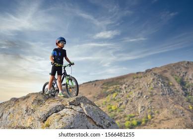 Fröhlicher Junge von 7 Jahren Spaß im Herbstpark mit einem Fahrrad an schönen Herbsttag. Aktives Kind mit Fahrradhelm