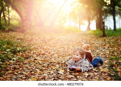 Happy kid boy in autumn park lying in fall yellow leaves and having fun, lens flare added