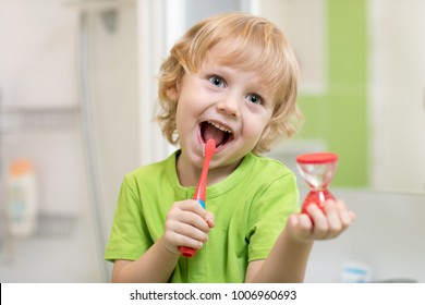Happy kid boy brushing teeth near mirror in bathroom. He is monitoring lasting of cleaning action with hourglass.