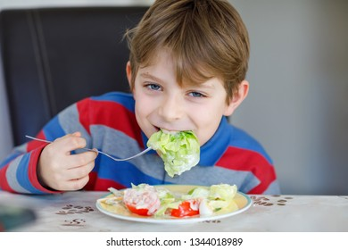 Happy kid boy eating fresh salad with tomato, cucumber and different vegetables as meal or snack. Healthy child enjoying tasty and fresh food at home or at school canteen. - Shutterstock ID 1344018989