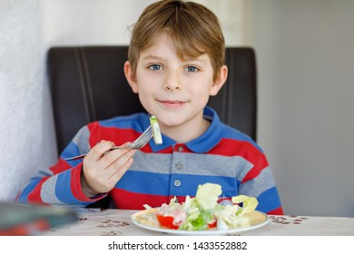 Happy kid boy eating fresh salad with tomato, cucumber and different vegetables as meal or snack. Healthy child enjoying tasty and fresh food at home or at school canteen. - Shutterstock ID 1433552882
