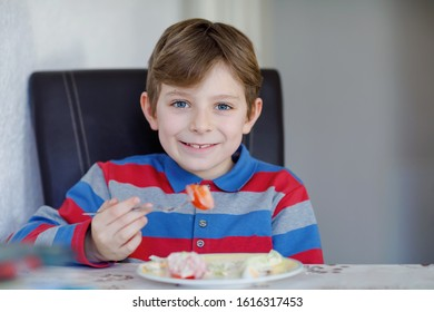 Happy kid boy eating fresh salad with tomato, cucumber and different vegetables as meal or snack. Healthy child enjoying tasty and fresh food at home or at school canteen. - Shutterstock ID 1616317453