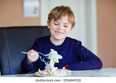 Happy kid boy eating fresh salad with tomato, cucumber and different vegetables as meal or snack. Healthy child enjoying tasty and fresh food at home or at school canteen. - Shutterstock ID 1936949320