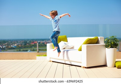 happy kid, boy jumping from the couch on roof top terrace at warm sunny day