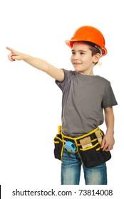 Happy kid boy with orange helmet pointing away isolated on white background