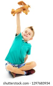 Happy kid boy plays with wooden toy airplane.Isolated on white background.