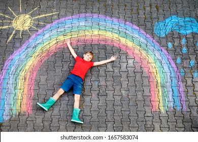 Joyeux garçon en bottes en caoutchouc avec le soleil arc-en-ciel et des nuages avec des gouttes de pluie peintes avec des craies colorées sur le sol ou l'asphalte en été. Loisirs créatifs pour les enfants en plein air en été