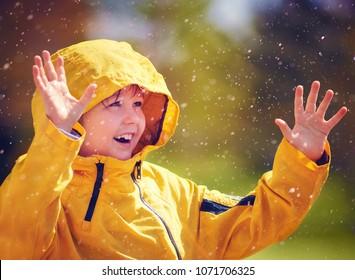 happy kid catching rain drops in spring garden