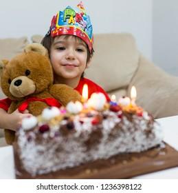 Happy kid celebratibg his birthday with his stuffed bear