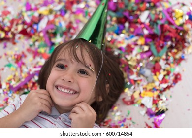 Happy kid celebrating party with blowing confetti while lying on the floor
