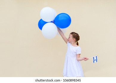 Happy kid, cute little caucasian girl (age 8-9) with blue and white balloons ans Israel flag.Patriotic holiday Independence day Israel - Yom Ha'atzmaut concept.Copy space for text.