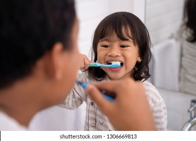 happy kid and dad having fun while brushing their teeth together in the bathroom sink