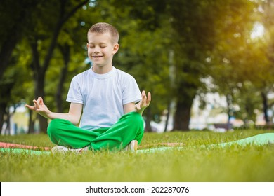 happy kid is doing exercises in the summer park