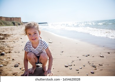 Happy kid dressed fashion shirt sit on the seaside sandy beach and playing with stones