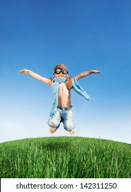 Happy kid dressed as a pilot jumping in green field against blue sky. Summer vacation concept