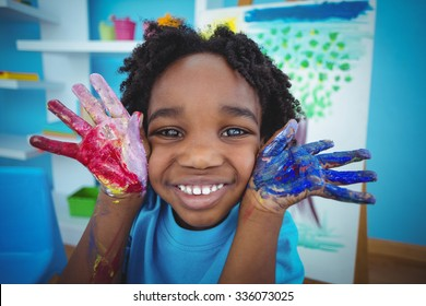 Happy kid enjoying arts and crafts painting with his hands