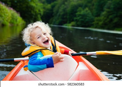 Happy kid enjoying kayak ride on beautiful river. Little curly toddler boy kayaking on hot summer day. Water sport and camping fun. Canoe for children. Funny child with vessel in a boat