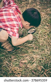 Happy kid enjoying in nature. Young boy exploring nature at ground with magnifying glass. Outdoors in the day time. Vintage style.
