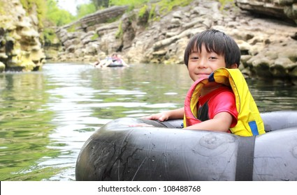 Happy kid floating on inflatable tube in river during vacation